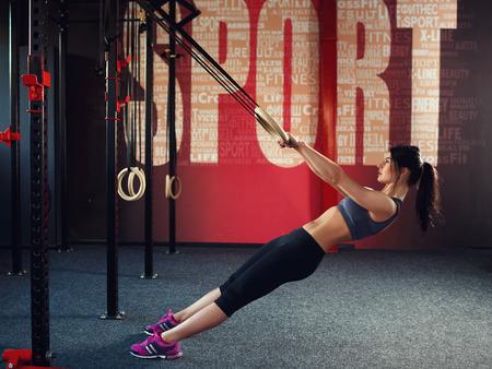and athlete: Entrenamiento Crossfit en el anillo. Fitness mujer sostiene sesi�n de entrenamiento crossfit en los anillos en el gimnasio. Mujer muscular aspecto cauc�sico, morena, se dedica a la gimnasia