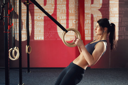 caucasian appearance: Crossfit workout on ring. Fitness woman holds training session crossfit on the rings in the gym. Muscular woman Caucasian appearance, brunette, is engaged in the gym