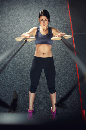 Crossfit Workout auf Ring. Fitness Frau hält Training crossfit an den Ringen in der Turnhalle. Muskulöse Frau Europäischer Abstammung, brünett, wird in der Turnhalle engagiert Standard-Bild - 38651159