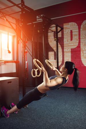 gym: Entrenamiento Crossfit en el anillo. Fitness mujer sostiene sesi�n de entrenamiento crossfit en los anillos en el gimnasio. Mujer muscular aspecto cauc�sico, morena, se dedica a la gimnasia
