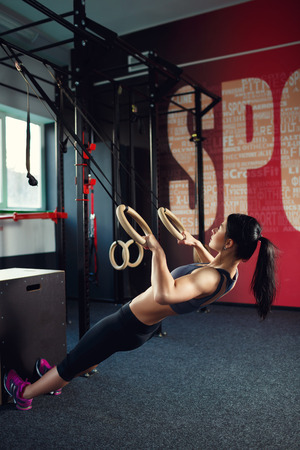 Crossfit workout on ring. Fitness woman holds training session crossfit on the rings in the gym. Muscular woman Caucasian appearance, brunette, is engaged in the gym