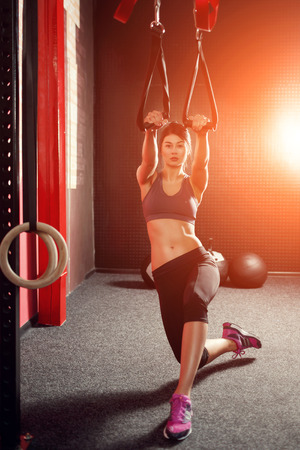 Crossfit training TRX straps. Young attractive brunette engaged cross fit on the suspension in the gym.