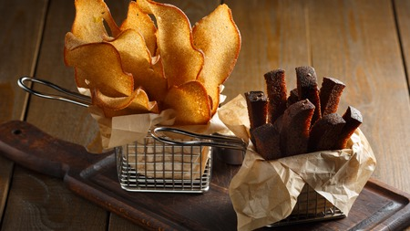 Appetizing fried golden brown croutons of rye and wheat bread in a metal basket on a brown wooden , backlit, close-up photo