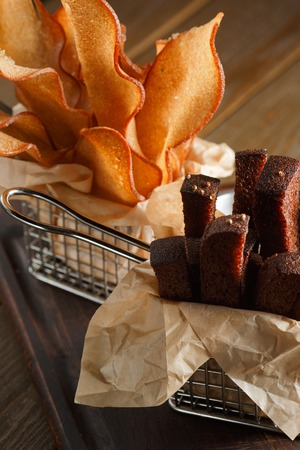 Appetizing fried golden brown croutons of rye and wheat bread in a metal basket on a brown wooden background, backlit, close-up photo