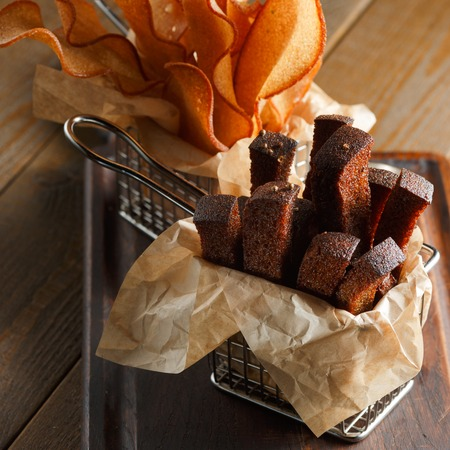 Appetizing fried golden brown croutons of rye and wheat bread in a metal basket on a brown wooden , backlit, close-up