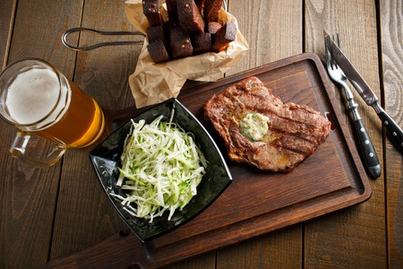 Delicious fried steak with butter and herbs, black plate of salad with fresh cabbage, beer and rye toast on dark wooden