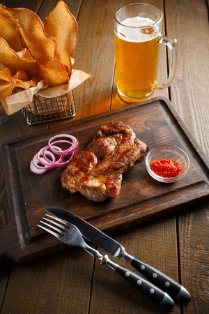 A delicious steak with chili sauce and chopped onion rings, chips of white bread in a metal basket and a glass of beer on a dark wooden