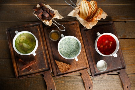 Three different traditional Ukrainian Russian cuisine, chicken broth with egg, okroshka and red borsch on wooden boards with rye and wheat bread, top view