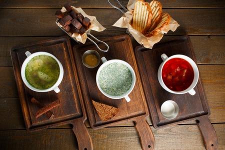 sopa de pollo: Tres cocina ucraniana tradicional diferente de Rusia, el caldo de pollo con huevo, Okroshka y borsch rojo sobre tablas de madera con centeno y pan de trigo, vista desde arriba