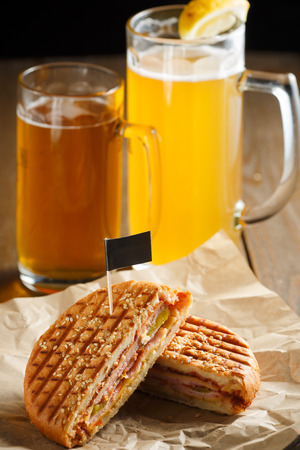 One burger with ham, onion, cucumber and cheese on a wooden plate sprinkled with sesame seeds, paper napkins, small black flag and two glasses of beer on a brown wooden , close-up photo