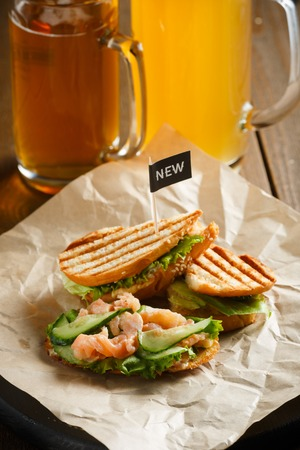 near beer: Sandwich with red fish, cucumbers and lettuce, with a black flag new served on a wooden plate with a paper towel, stand near by two glasses of beer on a wooden table, side view