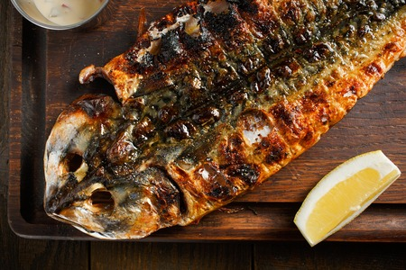 Baked mackerel, served on a wooden board with lemon sauce photo