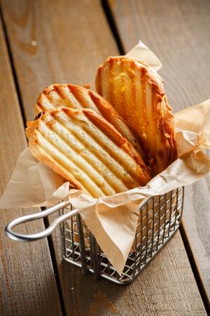 canasta de pan: Rebanadas tostadas de pan con una corteza dorada prolijamente apilados en un soporte de metal en un marrón de madera
