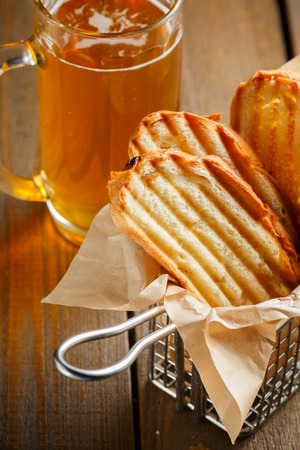 neatly stacked: Toasted slices of bread with a golden crust neatly stacked in a metal stand on a wooden brown and a glass of beer