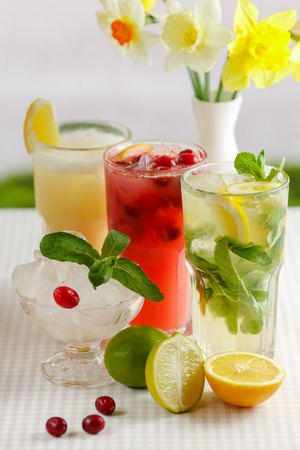 mohito: Three glasses of refreshing drink Mohito, classic mint, cranberry and orange on a table with slices of lemon, lime, a bowl with ice and yellow flowers