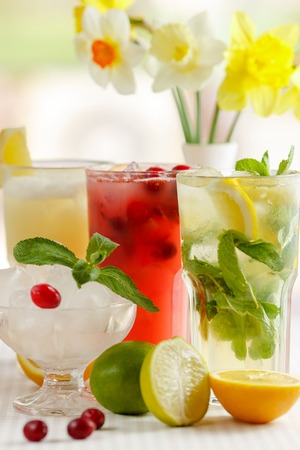 Three glasses of refreshing drink Mohito, classic mint, cranberry and orange on a table with slices of lemon, lime, a bowl with ice and yellow flowers