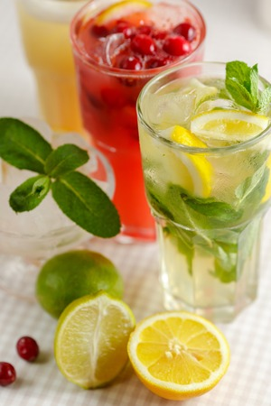 Three glasses of refreshing drink Mohito, classic mint, cranberry and orange on a table with slices of lemon, lime and a bowl of ice