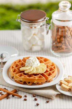 Belgian waffles with bananas and whipped cream, decorated with caramel sauce and powdered sugar on the table with a cup of coffee, coffee beans with cinnamon and two glass jars photo