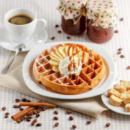 Belgian waffles with bananas and whipped cream, decorated with caramel sauce and powdered sugar on the table with a cup of coffee, coffee beans with cinnamon and two glass jars Foto de archivo
