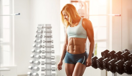 tanned body: Young muscular woman bodybuilder with white hair and tanned body posing in white gym at the counter with dumbbells