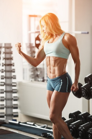 tanned body: Brutal blond with a muscular, tanned body, straining biceps and abdominal muscles against the window in the gym, vertical frame with space for text
