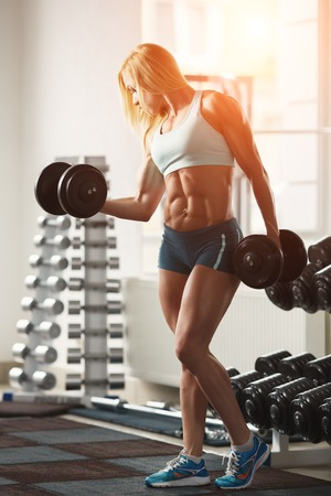 Strong woman bodybuilder with white hair and tanned body pumps up the muscles lifting dumbbells in the gym. Vertical frame with space for text