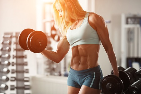 白い髪と日焼けした体と強い女性ボディービルダーは、ジムでダンベルを持ち上げる筋肉をポンプします。テキスト用のスペース、水平フレーム