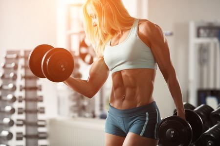 pesas: Culturista Mujer fuerte con el pelo blanco y cuerpo bronceado bombas hasta los músculos de elevación pesas en el gimnasio. Marco horizontal con espacio para texto Foto de archivo