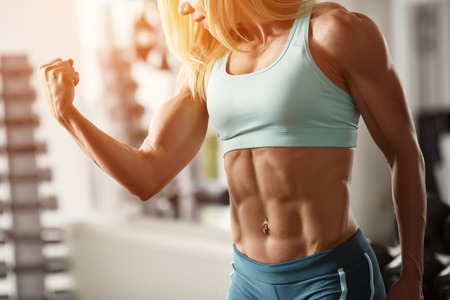 Brutal blond with a muscular, tanned body, straining biceps and abdominal muscles against the window in the gym, part of the body, horizontally frame Stock Photo