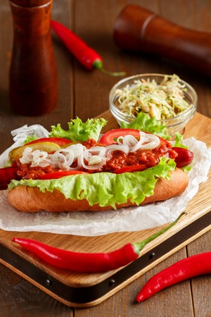 close up food: Close-up of spicy hot-dog on wooden cutting board