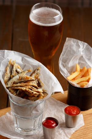 sprat: Close-up of beer snacks, sprat and french fries with gravy and glass of beer on wooden table Stock Photo
