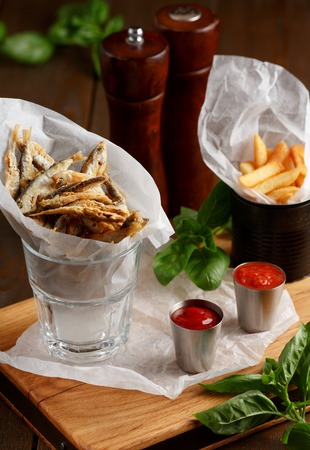 sprat: Close-up of beer snacks, sprat and french fries with gravy on wooden table