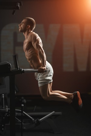 Strong muscular bodybuilder doing exercise on bars in the gym