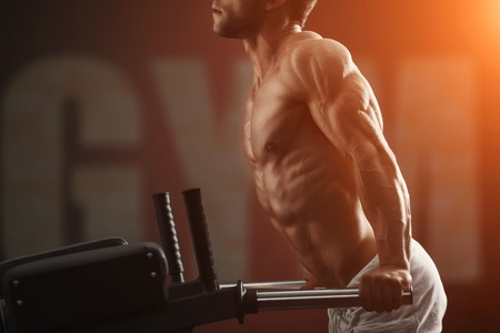fit man: Strong muscular bodybuilder doing exercise on bars in the gym