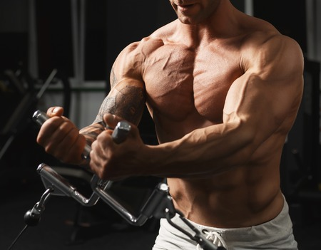 male bodybuilder: Strong muscular bodybuilder doing exercise on the chest in the crossover in the gym