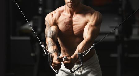 bodybuilder: Culturista musculoso fuerte haciendo ejercicio en el pecho en el cruce en el gimnasio