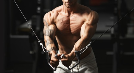 Strong muscular bodybuilder doing exercise on the chest in the crossover in the gym