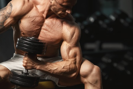 Strong muscular bodybuilder doing exercise with dumbbell in the gym Stock Photo