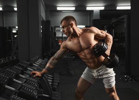 muscular: Culturista musculoso fuerte haciendo ejercicio con pesas en el gimnasio