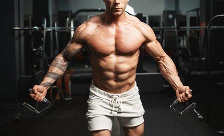 culturista: Culturista musculoso fuerte haciendo ejercicio en el pecho en el cruce en el gimnasio