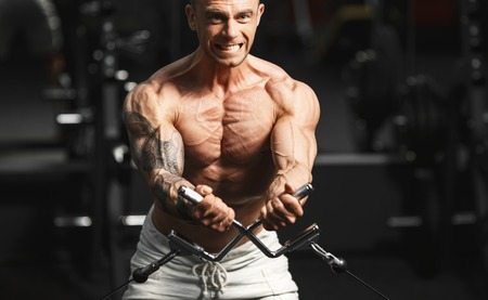 crossover: Strong muscular bodybuilder doing exercise on the chest in the crossover in the gym
