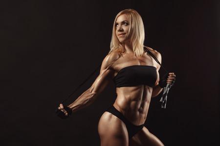 cuerpo perfecto femenino: Confiado joven muscular aptitud femenina mirando a otro lado y posando con saltar la cuerda en el estudio sobre un fondo negro. Vista frontal de la mujer culturista con saltar la cuerda
