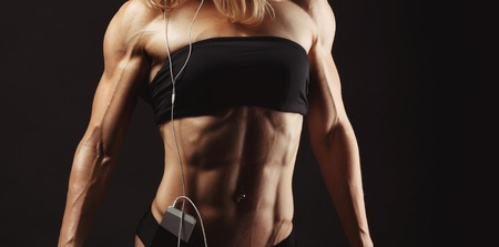 female hand: Studio shot of muscular young woman listening music on mobile phone against black background. Attractive blond bodybuilder with a mobile phone. Space for text on the right side