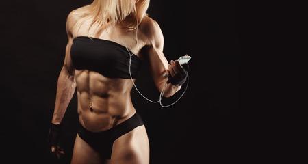 mujer deportista: Estudio tirado de musculoso joven música mujer escucha en el teléfono móvil contra el fondo negro. Fisicoculturista rubia atractiva con un teléfono móvil. Espacio para el texto en el lado derecho