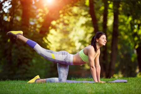 Young smiling woman doing fitness exercises in the park on the green grass. Fitness training in the sunlight.