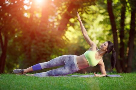 Mujer haciendo ejercicios de fitness sonrientes en el parque en la hierba verde. Entrenamiento de la aptitud en la luz del sol. Foto de archivo - 43152808