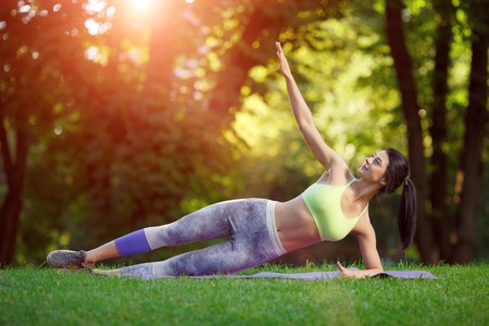 Young smiling woman doing fitness exercises in the park on the green grass. Fitness training in the sunlight. Stock Photo - 43152808