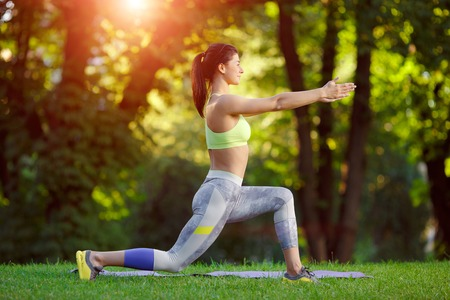 'fit body': Young smiling woman doing fitness exercises in the park on the green grass. Fitness training in the sunlight.