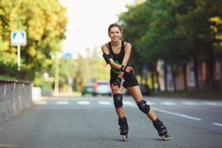 Beautiful, athletic, young woman in black sportswear, to roller skate on the road. Cheerful girl on roller skates in the rays of the setting sun. Active lifestyle