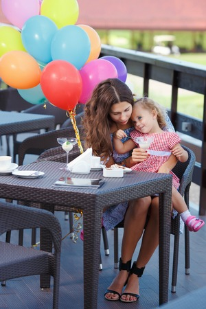 small child: Happy mother and daughter with balloons in the background, eating ice cream and drinking coffee outdoors. Family sitting at a table in the outdoor cafe and eating ice cream. Stock Photo
